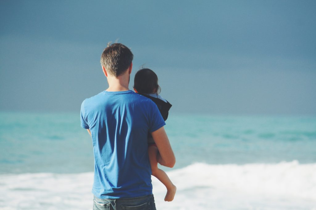 A dad holding his child and watching the sea