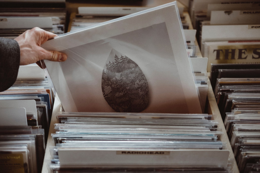 A hand picking out a record from a stack, illustrating the selection process.