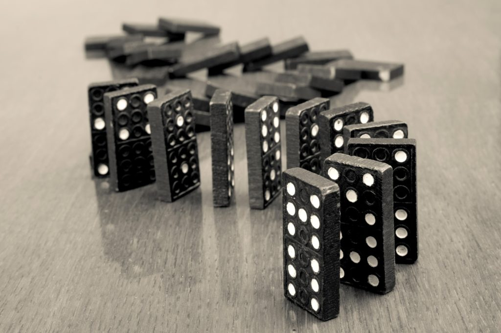 A set of dominoes, some standing, some fallen, that illustrated the sequencing process.