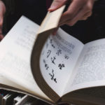 A man flipping through the pages of a book, used as an illustration for skimming