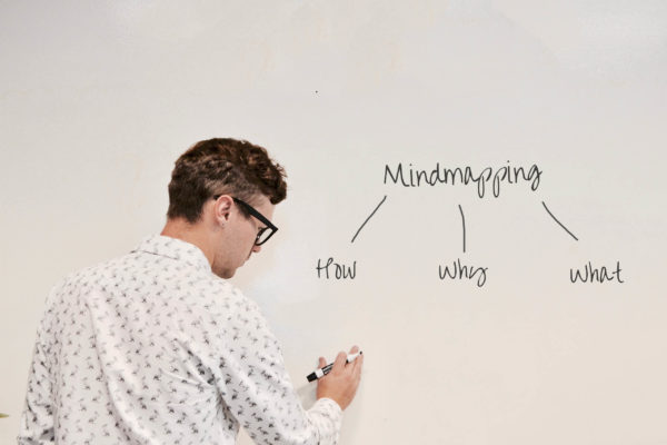 A man writing a simple mind map on mind mapping on a whiteboard
